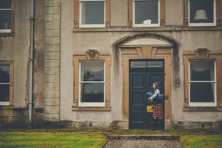 piper waiting for the bride outside lochnell castle