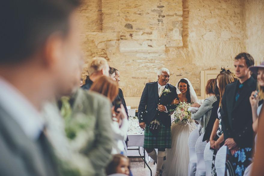 bride walking down the isle in lochnell castle